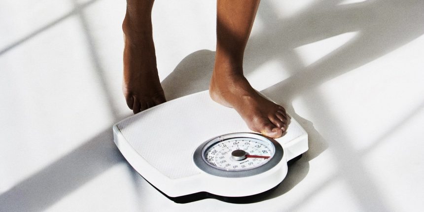 Cropped look of young woman weighing herself.